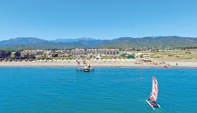 """<div style=""""text-align: justify;"""">Het TUI SENSATORI Resort Barut Fethiye ligt direct aan het zand/kiezelstrand, op 13 km van het centrum van Fethiye. De Dolmus stopt vlak voor het hotel en brengt je snel tot in het centrum. Het hotel ligt op 45km van de luchthaven, en je vakantie begint meteen bij aankomst, want je transfer tot aan het hotel is inbegrepen.</div>"""