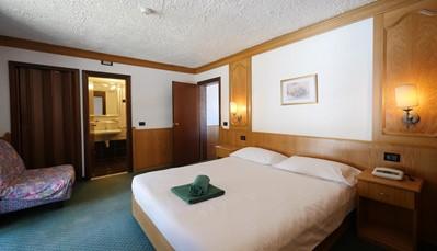 """<div style=""""text-align: justify;"""">De 135 kamers bevinden zich in meerdere gebouwen, die allemaal met gangen verbonden zijn. Stuk voor stuk zijn ze comfortabel en gezellig ingericht. Je vindt er een badkamer met douche en haardroger, flatscreen tv, minibar, telefoon en een minisafe. Kinderbedjes zijn&nbsp;mogelijk op aanvraag.&nbsp;</div>"""