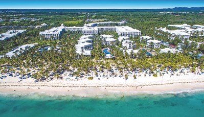 """<p style=""""text-align: justify;"""">Het hotel ligtdirect aan het Arena Gorda-strand, en maakt deel uit van hetRIU resort samen met de hotels Riu Palace Macao, Riu Palace Punta Cana, Riu Naiboa en het Riu Bambu. Je verblijft hier op40 km van Higüey, en op± 25 km van de luchthaven (transfer heen en terug inbegrepen).</p>"""