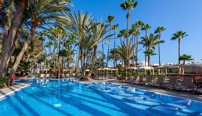 """<p style=""""text-align: justify;"""">Het hotel ligt vlak aan het strand van Maspalomas (directe toegang via de tuin), dicht bij 'El Faro' en de duinen van Maspalomas. Je vindt shops op 50m, enPlaya del Inglés ligt op 5 km. 200 m van het hotel kan je een bushalte vinden, en de luchthaven ligt op± 37 km van de luchthaven (transfer heen en terug inbegrepen).</p>"""
