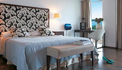 """<div style=""""text-align: justify;"""">De 35 kamers en suites van het hotel zijn comfortabel en eigentijds ingericht, met elk een eigen design. Ze zijn voorzien van exclusieve faciliteiten, zoals een digitale satelliet-tv van Bang &amp; Olufsen. Verder is elke kamer ingericht met &nbsp;een marmeren badkamer, sofa, koffie/thee faciliteiten en een safe. Je kijkt uit over een van de tuinen of de zee. De luxueuze suites hebben altijd zeezicht.</div>"""