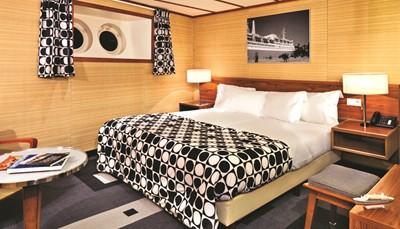"""<div style=""""text-align: justify;"""">Waar vroeger de hutten van het stoomschip waren, vind je nu 254 kamers in een fifties decor naar keuze: Original, Manhattan of Bahamas. Elke kamer is uniek in vorm, inrichting en kleur en is gelegen op het B Deck, A Deck, Main Deck, Lower Promenade Deck, Boat Deck en Sun Deck. Ze zijn uitgerust met een twin of dubbel bed, badkamer met douche, gratis wifi, klimaatbehandeling, flatscreen TV, Nespresso-apparaat en waterkoker, (laptop)kluis en föhn.</div>"""