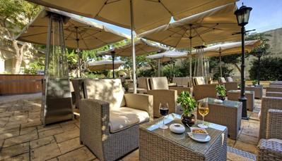 """<div style=""""text-align: justify;"""">Het vijfsterrenhotel Corinthia Palace is ondergebracht in een luxueuze villa die dateert uit de 19de eeuw. Dit vredig resort is centraal gelegen op Malta en wordt omringd door schitterende tuinen. In een landelijk decor geniet je hier van uitmuntende gastronomie en voortreffelijke faciliteiten, onder meer buiten- en binnenzwembaden en een wellnesscentrum. Traditie, charme en prestige worden gekoppeld aan authentieke Maltese gastvrijheid. Een onvergetelijk en ontspannen verblijf in een vaak bekroond hotel.</div>"""