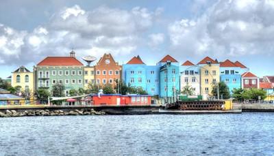 """<div style=""""text-align: justify;"""">Wuivende palmbomen, bruisende stadjes en het heerlijk tropische klimaat maken van Curaçao de perfecte vakantiebestemming. Je kunt in een van de vele baaien naar hartenlust zonnen, zwemmen of snorkelen. Wie liever op het droge blijft, kan de vrolijk gekleurde handelshuizen in Willemstad bezoeken, of met de fiets een van de nationale parken verkennen.</div>"""