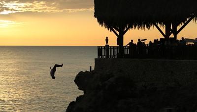 """<span style=""""color:#FF0000;""""><strong>3. Zie de spectaculaire rotsduikers bij Rick's Café</strong></span><br /> Rick's Café is gelegen op de top van een klif en geeft dus een fantastisch uitzicht over de Caraïbische zee. Het is dé beste plek om te genieten van een mooie zonsondergang en verdient dus zeker een plaatsje op je bucket list. Terwijl je geniet van je drankje, de live reggae muziek en de ondergaande zon, kun je er kijken naar de Jamaicaanse rotsduikers die vanaf duizelingwekkende hoogte in het water springen."""