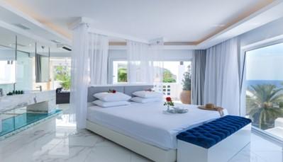 """<div style=""""text-align: justify;"""">Het hotel bestaat uit 318 luxueuze kamers en suites. De kamers zijn licht en modern ingericht in een stijl die geïnspireerd is door de Griekse eilanden. Alle kamers hebben minstens een 40 inch televisie, een uitstekende wifiverbinding, een minibar en alle moderne faciliteiten. Je hebt de keuze uit verschillende kamertypes, gaande van een standaard kamer tot een luxe suite, een familiesuite of zelfs een eigen villa. Vraag ons gerust meer informatie over de beschikbaarheid van de verschillende kamertypes.</div>"""