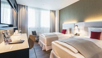 """<p style=""""text-align: justify;"""">De kamers zijn ruim, modern, stijlvol en verzorgd. Elke kamer beschikt over een badkamer met regendouche, haardroger, toilet, airco, koffiezetapparaat, minikoelkast, eenflatscreen tv en een gratis minisafe. Het hotel torent boven de stad uit, dus afhankelijk van de verdieping waarop je verblijft, heb je een mooi uitzicht over de skyline van Berlijn. Je hebt gratis internet op de kamer.</p>"""
