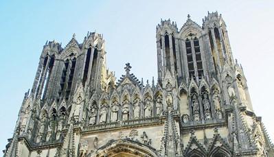 """Nadien rijden we verder naar het centrum van Reims voor een stadsrondrit. We krijgen er een geleid bezoek aan de kathedraal Notre Dame. Vervolgens eten we ons middagmaal in het centrum van Reims. Dan rijden we langs de """"Route Touristique du Champagne"""" door het Parc Régional de la Montagne de Reims naar Ecueil voor een bezoek en een proeverij bij een Champagneproducent."""
